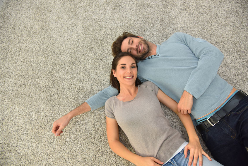 couple laying on cleaned carpets